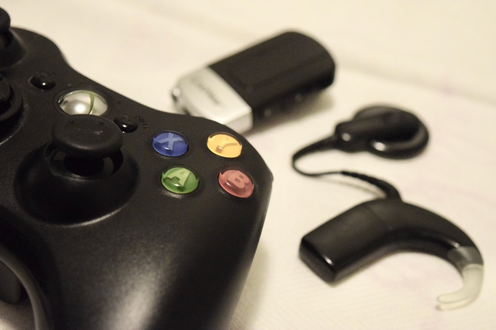 An Xbox controller with a hearing device in the background